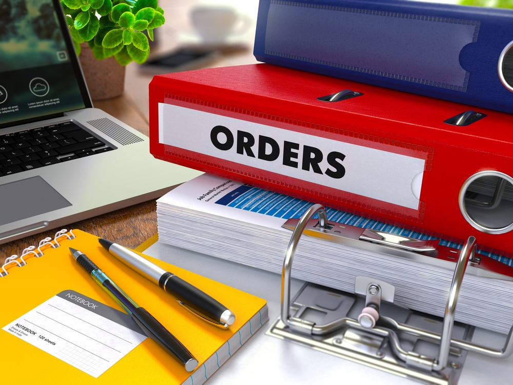 Red Ring Binder with Inscription Orders on Background of Working Table with Office Supplies, Laptop, Reports. Toned Illustration. Business Concept on Blurred Background..jpeg